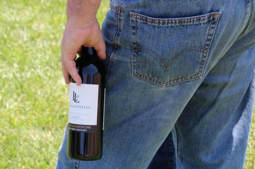 A photo of Lucas & Lewellen Tasting Room Manager Andy in jeans holding a wine bottle